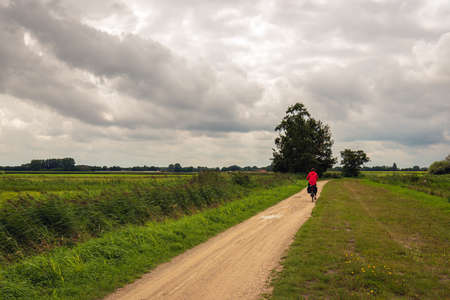 Woman with a bright red jacket is cycling on a sandy path through a Dutch peat meadow area in the province of North Brabant. It's summer but the sky is overcast.