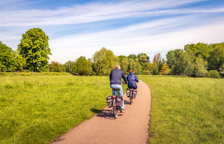 A man and a woman are cycling on a curved bicycle path in a Dutch nature reserve. It's a sunny day in the spring season.