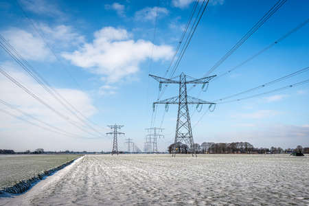 Power lines and pylons in a winter landscape. A layer of untouched snow is on the field. The sky is bright blue with some narrow white clouds. The photo was taken in the Dutch province of Noord-Brabant.