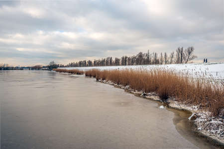 Snowy embankment along a frozen lake. Yellow reed plants are along the lake. The sky is covered with snow clouds. Two unrecognizable people are walking on the dike. It's winter in the Netherlands. Standard-Bild