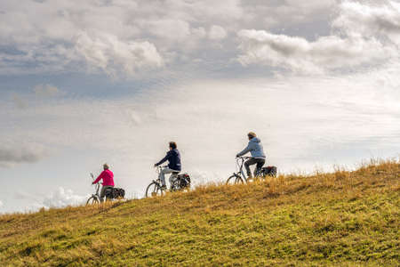 Three unidentified women cycle one behind the other with their electric bicycles on a Dutch dike. It's a sunny day in the autumn season. The grass on the embankment of the dike is yellow and withered