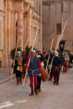sword act: MDINA, MALTA - APRIL 14  People in medieval costume parading in the Medieval Mdina festival in Mdina, Malta on April 14, 2012
