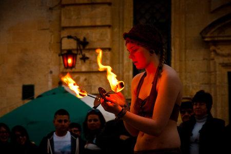 sword act: MDINA, MALTA - APRIL 14  Fire artist takes part in the Medieval Mdina festival in Mdina, Malta on April 14, 2012