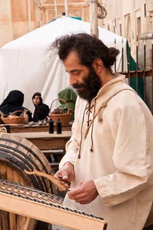 sword act: MDINA, MALTA - APRIL 14  Medieval style musician takes part in the Medieval Mdina festival in Mdina, Malta on April 14, 2012 Editorial