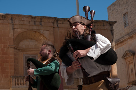 sword act: MDINA, MALTA - APRIL 14  Medieval style musicians group takes part in the Medieval Mdina festival in Mdina, Malta on April 14, 2012