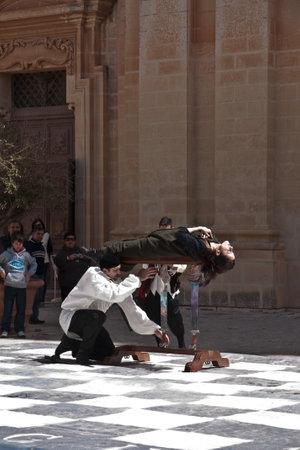 sword act: MDINA, MALTA - APRIL 14  Medieval style magician takes part in the Medieval Mdina festival in Mdina, Malta on April 14, 2012
