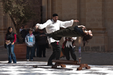 sword act: MDINA, MALTA - APRIL 14  Medieval style magician takes part in the Medieval Mdina festival in Mdina, Mdina, Malta on April 14, 2012