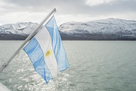 Argentinas flag waving in Lago Argentino, the Patagonian province of Santa Cruz, Argentina photo