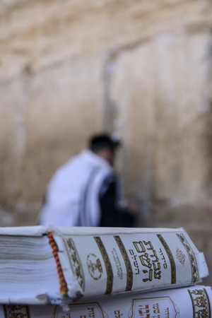 kippah: JERUSALEM - JULY 31 - Orthodox Jews prays at the Western Wall, behind praying book  Siddur  - July 31, 2013 in the old city of Jerusalem, Israel  This is the holiest place in Jewish tradition Editorial