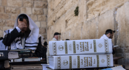 JERUSALEM - JULY 31 - Orthodox Jews prays at the Western Wall, behind praying book  Siddur  - July 31, 2013 in the old city of Jerusalem, Israel  This is the holiest place in Jewish tradition