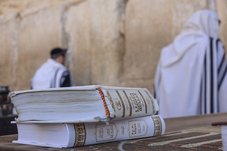 siddur: JERUSALEM - JULY 31 - Orthodox Jews prays at the Western Wall, behind praying book  Siddur  - July 31, 2013 in the old city of Jerusalem, Israel  This is the holiest place in Jewish tradition Editorial