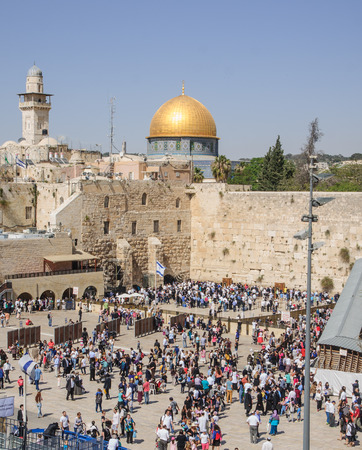JERUSALEM, ISRAEL - APRIL 17, 2014  The Western Wall crowded with Passover prayers, and the Dome of the Rock in the background, in the old city of Jerusalem, Israel