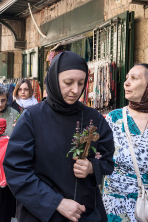 JERUSALEM - APRIL 18, 2014  Pilgrims from all over the world commemorating the crucifixion of Jesus Christ by carrying a cross along via dolorosa, on good Friday, in the old city of Jerusalem, Israel