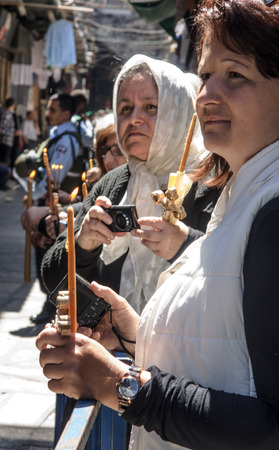 JERUSALEM - APRIL 18, 2014  A group of Pilgrims holding candles while watching the cross carrying ceremonies, along Via Dolorosa, on Good Friday, in the old city of Jerusalem, Israel