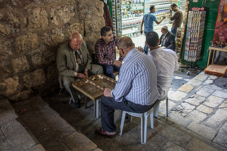 JERUSALEM - APRIL 18, 2014  Typical street scene of backgammon players, in the old city of Jerusalem, Israel