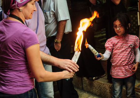 JERUSALEM - APRIL 19, 2014  The holy fire from the holy fire ceremony the Church of the Holy Sepulcher shared between pilgrims along the Via Dolorosa Street, on Holy Saturday, in Jerusalem, Israel