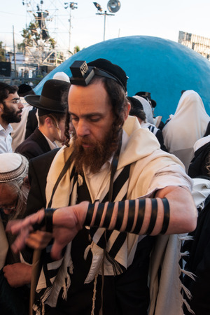 tefillin: MERON, ISRAEL - MAY 18, 2014  An orthodox Jew putting on his tefillin, near the tomb of Rabbi Shimon, at the annual hillulah of Rabbi Shimon Bar Yochai, in Meron, on Lag BaOmer Holiday