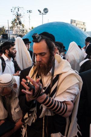 rabbi: MERON, ISRAEL - MAY 18, 2014  An orthodox Jew putting on his tefillin, near the tomb of Rabbi Shimon, at the annual hillulah of Rabbi Shimon Bar Yochai, in Meron, on Lag BaOmer Holiday