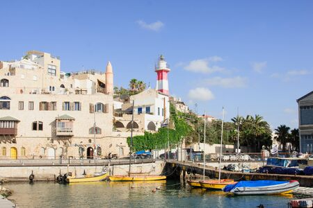 TEL-AVIV - JULY 13, 2014  Boats and lighthouse in the old Jaffa Port  Jaffa Port in an ancient port with 3000 years of history  Now part of the city of Tel-Aviv Yafo, Israel
