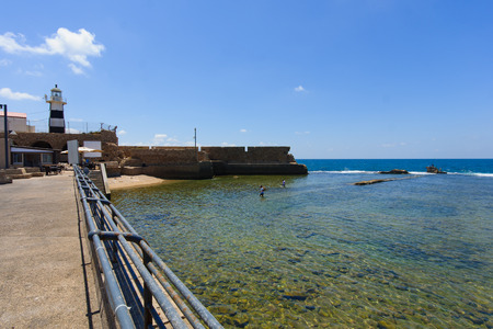 ACRE, ISRAEL - AUGUST 08, 2014  Local fishermen near the lighthouse and the old Templars crusader fort in the old city of Acre, Israel