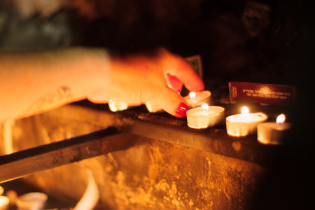 selichot: Jewish woman lights a candle, as part of Selichot tradition (request for forgiveness) at the tomb of Rabbi Yehuda Bar Ilai, on Yom Kippur eve, in Safed, Israel.