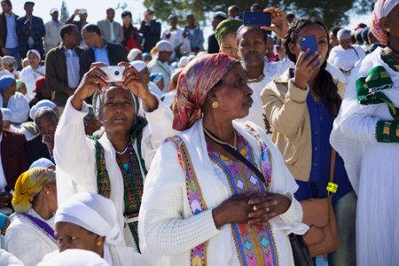 holiday prayer book: JERUSAL�N - 20 de noviembre 2014: las mujeres jud�as et�opes mezclan vieja tradici�n de ora, con dispositivos de documentaci�n modernos, en el Sigd, en Jerusal�n, Israel. El Sigd es una fiesta anual de los Judios de Etiop�a Editorial