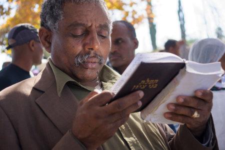 holiday prayer book: JERUSAL�N - 20 de noviembre 2014: Un hombre jud�o et�ope reza usando un libro de oraciones en el Sigd, en Jerusal�n, Israel. El Sigd es una fiesta anual de los Judios de Etiop�a Editorial