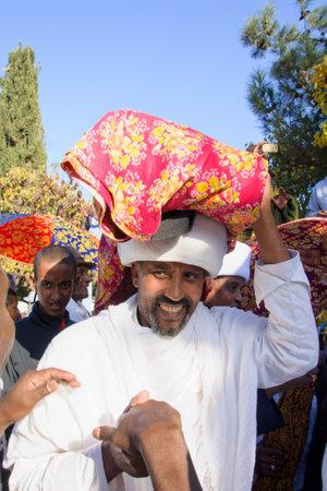 holiday prayer book: JERUSAL�N - 20 de noviembre 2014: Un Kes, l�der religioso de los Judios de Etiop�a, que lleva un libro de oraciones santa envuelto, al final de la Sigd anual de vacaciones ora, en Jerusal�n, Israel Editorial