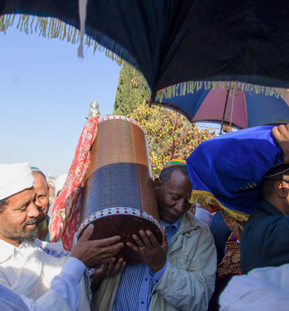 holiday prayer book: JERUSALEM - NOV 20, 2014: An Ethiopian Jewish man and a Kes, religious leader of the Ethiopian Jews, carrying the holy torah book, at the end of the annual Sigd holiday prays, in Jerusalem, Israel