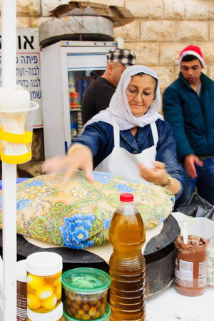 nazareth: NAZARETH, ISRAEL - December 19, 2014: A woman preparing pita bread, in a Christmas market food stall, in Nazareth, Israel