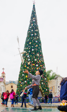 nazareth: NAZARETH, ISRAEL - December 19, 2014: Jugglers, local and visitors, and a Christmas tree, in the square of the Greek Orthodox Church of Annunciation, in Nazareth, Israel Editorial