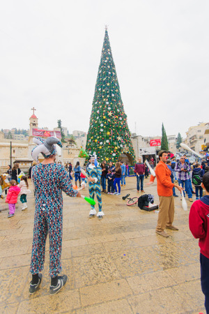 annunciation of mary: NAZARETH, ISRAEL - December 19, 2014: Jugglers, local and visitors, and a Christmas tree, in the square of the Greek Orthodox Church of Annunciation, in Nazareth, Israel Editorial
