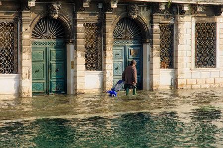 cope: VENICE, ITALY - FEB 02, 2015: People cope with the flooded street, in Cannaregio, Venice, Veneto, Italy