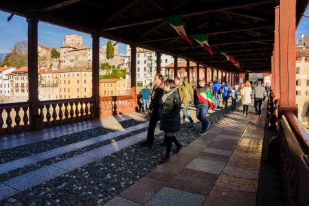 BASSANO DEL GRAPPA, ITALY - JAN 31, 2015: Scene of The Ponte Vecchio (or Ponte degli Alpini) bridge, with local and tourists, and the Brenta river, in Bassano del Grappa, Veneto, Italy