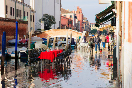 VENICE, ITALY - FEB 02, 2015: Typical canal and flooded street scene, with local and tourists, in Cannaregio, Venice, Veneto, Italy