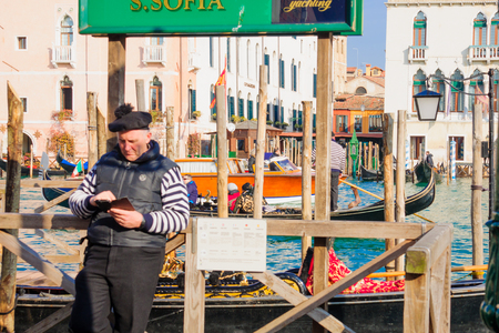 gondoliers: VENICE, ITALY - FEB 02, 2015: Typical canal scene of gondolas and gondoliers, in Venice, Veneto, Italy