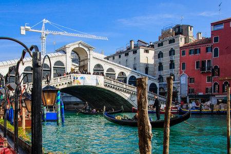 gondoliers: VENICE, ITALY - FEB 02, 2015: Scene of the Rialto Bridge, with gondolas and gondoliers, local and tourists, in Venice, Veneto, Italy