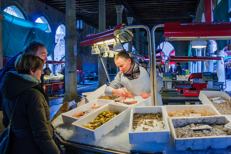 the merchant of venice: VENICE, ITALY - FEB 03, 2015: Market scene with sellers and shoppers in the rialto market, in Venice, Veneto, Italy