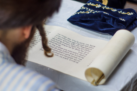 esther: JERUSALEM, ISRAEL - MAR 05, 2015: An ultra-orthodox Jew reads the book of Esther (the megillah), as part of the traditions of the holiday of Purim, in Jerusalem, Israel