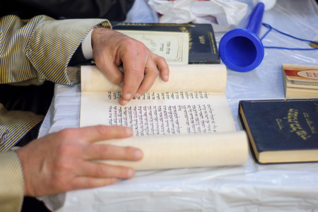 JERUSALEM, ISRAEL - MAR 05, 2015: An ultra-orthodox Jew reads the book of Esther (the megillah), as part of the traditions of the holiday of Purim, in Jerusalem, Israel