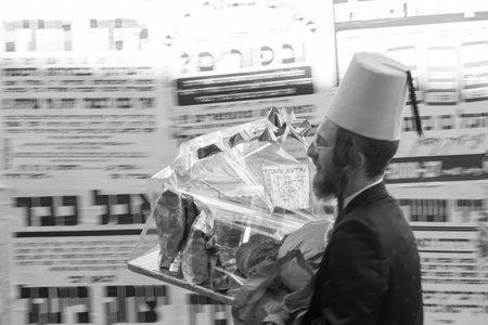 chassidim: GERUSALEMME, ISRAELE - 6 marzo 2015: Un Ebreo ultra-ortodosso offre doni alimentari (mishloach Manot), come parte delle tradizioni della vacanza di Purim, a Gerusalemme, Israele