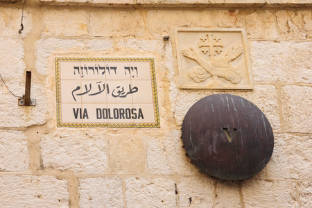 via dolorosa: A mark of station 5 of the Via Dolorosa, and a street sign, in the old city of Jerusalem, Israel