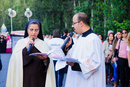 carmelite nun: HAIFA, ISRAEL - APR 19, 2015: Local nun and priest in a prayer to Mary, as part of the annual our lady of Mount Carmel parade, in Haifa, Israel. This annual event commemorates the hiding of Mary statue in WWI