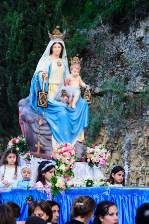 HAIFA, ISRAEL - APR 19, 2015: The statue of Mary is carried up by the local Christian community members, in the annual our lady of Mount Carmel parade, in Haifa, Israel. This annual event commemorates the hiding of Mary statue in WWI