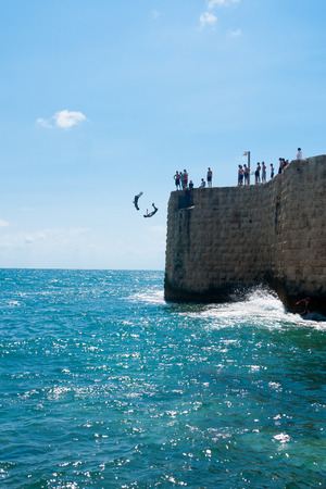 continuously: ACRE, ISRAEL - JUNE 27, 2009: Young men jumps to the sea from the top of the ancient walls of Acre, Israel. Acre is one of the oldest continuously inhabited sites in the world.