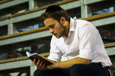 MERON ISR  MAY 06 2015: An orthodox Jew read a prayer book at the annual hillulah of Rabbi Shimon Bar Yochai in Meron on Lag BaOmer Holiday. Its an annual celebration at the tomb of Rabbi Shimon