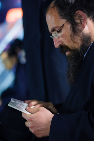 tefillin: MERON ISR  MAY 06 2015: An orthodox Jew read a prayer book at the annual hillulah of Rabbi Shimon Bar Yochai in Meron on Lag BaOmer Holiday. Its an annual celebration at the tomb of Rabbi Shimon