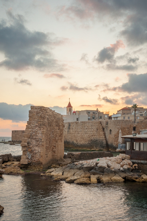 acre: ACRE ISRAEL  MAY 04 2015: Sunset scene of the old city walls St. John the Baptist church and local fishermen in the old city of Acre Israel