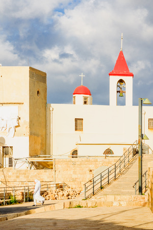acre: ACRE ISRAEL  MAY 04 2015: A nun walks away from St. John the Baptist church in the old city of Acre Israel Editorial