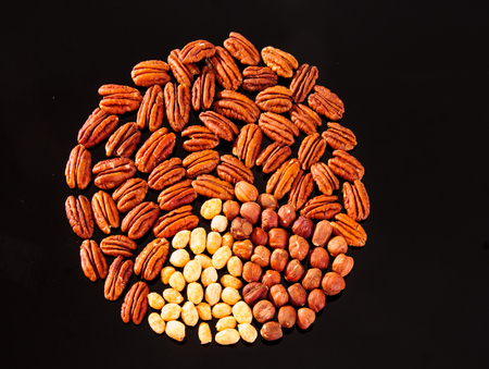 Assorted nuts (Pecan, Hazelnuts and Roasted Salted Peanuts) in a circle form on a black background